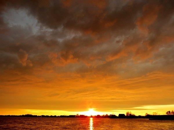 De zon ging fraai onder na passage van een onweersbui. Foto is van Ton Wesselius