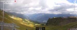 Een opklarend weerbeeld boven Wallis bij Crans-Montana. Een regenboog maakt het webcambeeld compleet. Bron: crans-montana.ch