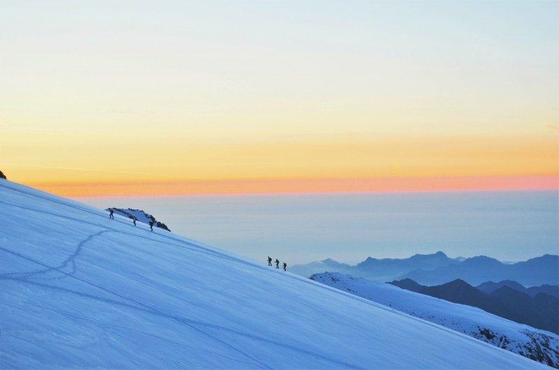 De zonsopkomst is een van de mooiste momenten in de Alpen. Een touwgroepje steekt hier de Indren gletsjer over.