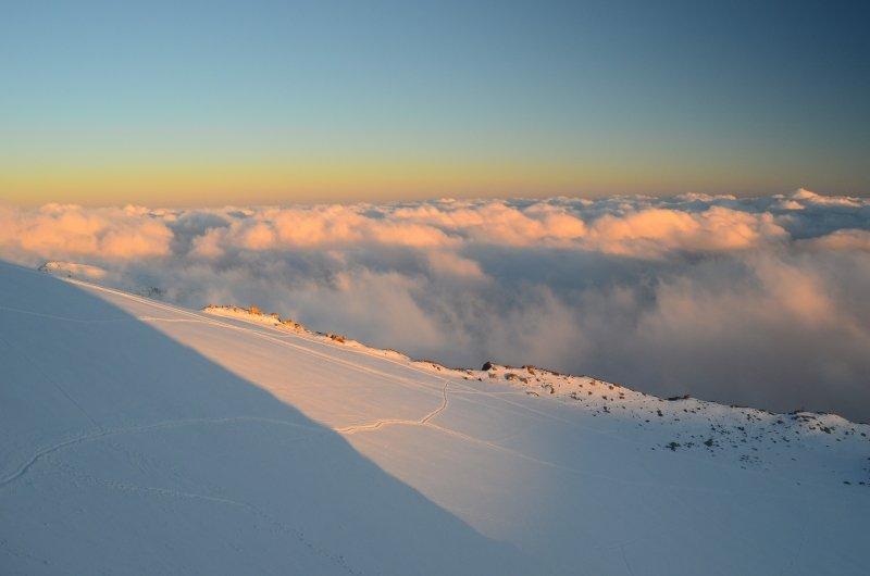 De zon gaat onder boven de Indren gletsjer, terwijl het dal zich vult met wolken