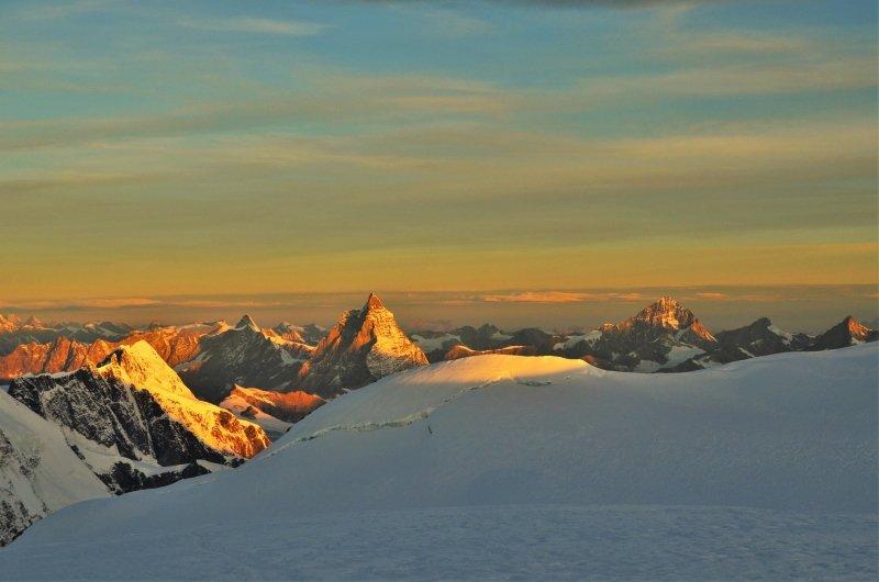 Op weg naar de top van de Zumsteinspitze genieten we andermaal van een weergaloze zonsopkomst. Het eerste licht valt op de Lyskamm, de Matterhorn en de Dent Blanche.