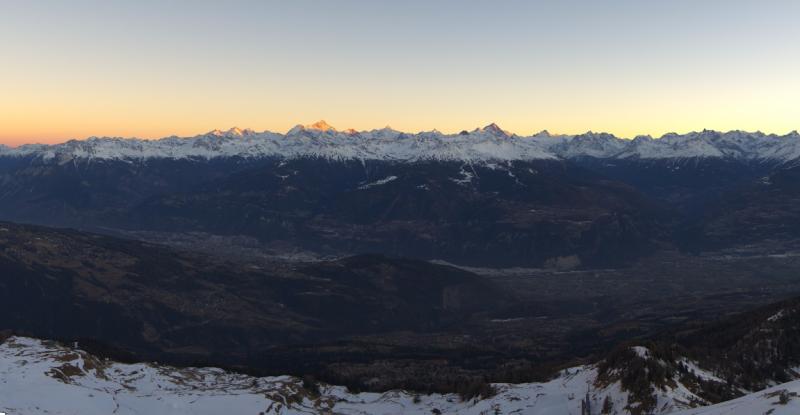 Prachtige zonsondergang bij Wallis waar de hoogste bergen van Zwitserland in de verte nog in de zon liggen. Bron: roundshot.com
