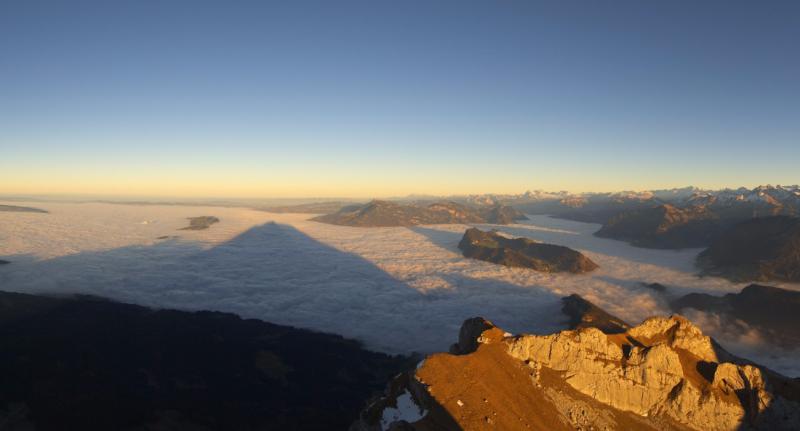 Prachtig beeld gisteren vanop Pilatus over Luzern. De lage bewolking plakt tegen de bergen. Tegelijk zien we de schaduw van nabij gelegen bergen op de wolken. Bron: roundshot.com